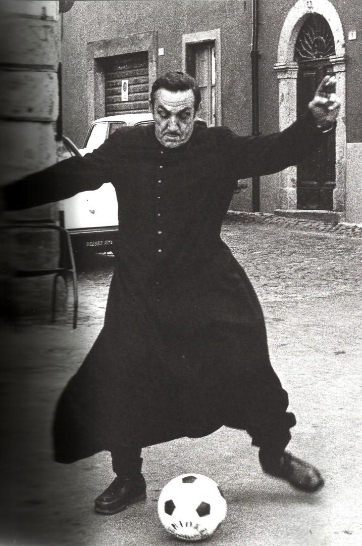 """A Roma Lino Ventura gioca a calcio, vestito da prete, durante le riprese del film di Duccio Tessari """"Uomini duri"""" (1973)."""