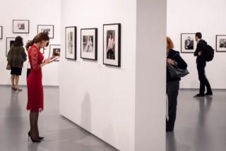 Una visitatrice rossovestita alla mostra moscovita dedicata alla grande fotografa italiana Elisabetta Catalano (1941-2015)
