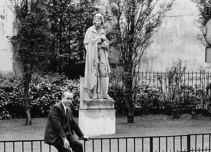 Fotografia di Ferdinando Scianna. Lo scrittore Leonardo Sciascia a Parigi, in Rue de la Seine, davanti alla statua di Voltaire. 1978.